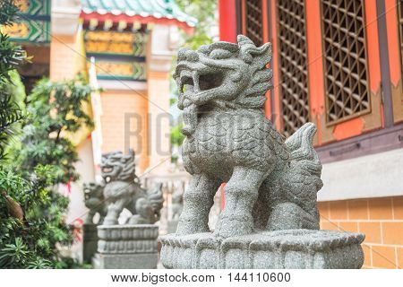Gray legendary lion statues in Wong Tai Sin Temple a famous tourist attraction of Hong Kong.