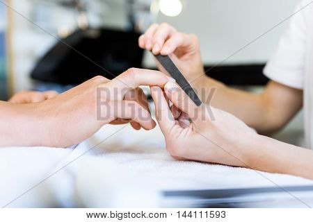 Portrait of young man doing manicure in salon. Beauty concept.