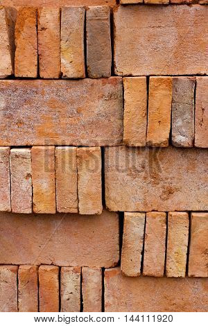 New red brick pavers stacked in rows like wall. Store of bricks ready for building or sale. Construction materials and outdoor storage. Abstract background.