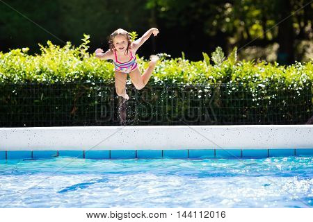 Happy little girl jumping into outdoor swimming pool in a tropical resort during family summer vacation. Kids learning to swim. Water fun for children.