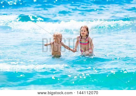 Happy children running and jumping in the waves during summer vacation on exotic tropical beach. Holiday on ocean coast for family with young kids. Boy and girl play at the sea learning to swim.