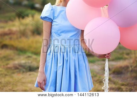 Woman holding air balloons in field