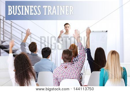 Business training concept. Young colleagues raising hands at the business meeting in office