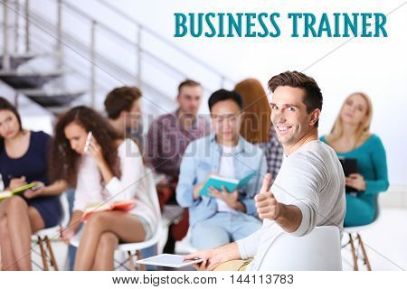Business training concept. Happy young man sitting in front of people at the office meeting