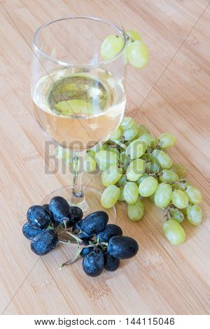 Branch of healthy grape fruit and a glass of white wine on a wooden board.