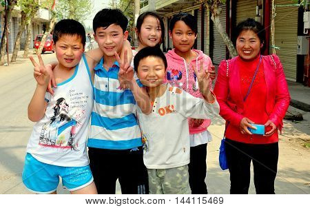 Pengzhou Township China - March 23 2013: Friendly Chinese school children with their teacher on the main street in Wan Jia Village