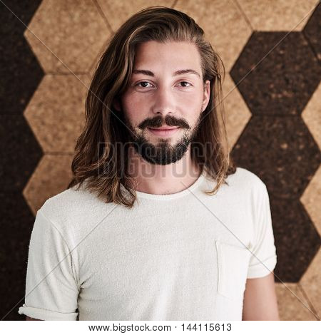 Young caucasian creative man with long brown hair wearing a white shirt in front of a cork wall with a hexagonal pattern and uniform tones.