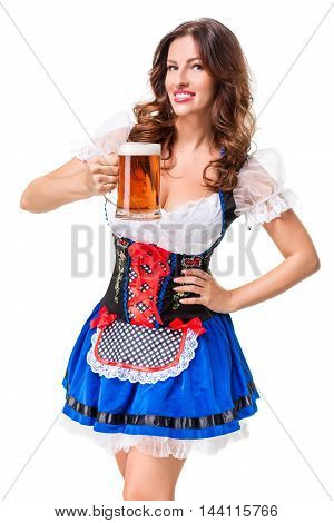 Beautiful young brunette girl in dirndl drinks out of oktoberfest beer stein. Isolated on white background.
