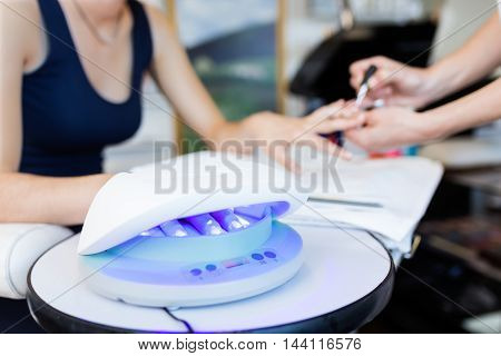 Portrait of young woman doing manicure in salon. Beauty concept.