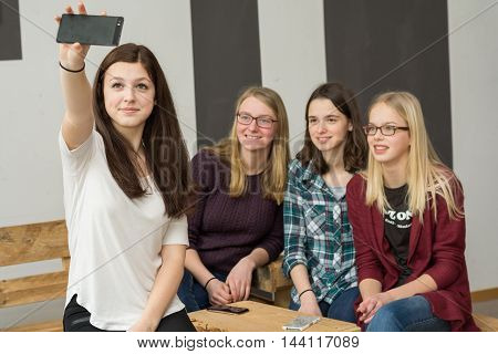 Teenager group with four girls making with a Smartphone Selfie