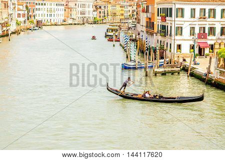 Venice, Italy - May 18, 2016: Gondolier swim in gondola on the Grand canal in Venice. Gondola is a traditional venetian boat and famous tourist attraction.
