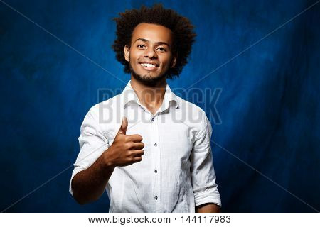 Young handsome african man in white shirt smiling, showing okay over blue background. Copy space.