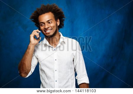 Young handsome african man in white shirt speaking on phone over blue background. Copy space.