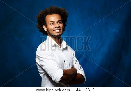 Young handsome african man smiling, looking at camera, posing with crossed arms over blue background. Copy space.