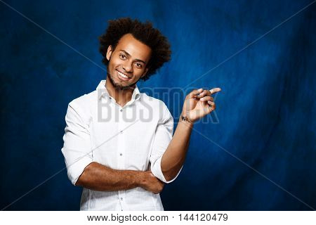 Young handsome african man in white shirt smiling, pointing finger in side over blue background. Copy space.