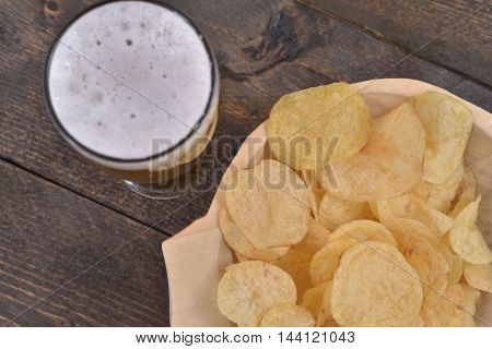 Gold salted potato chips in a wooden bowl on a rustic brown table with a beer glass, top view