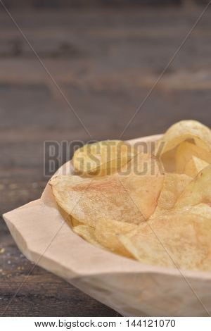 Gold salted potato chips in a wooden bowl on a rustic brown table