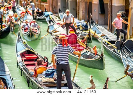 Venice, Italy - May 18, 2016: Gondoliers sail on gondolas full of tourists in the narrow water canal in Venice. Gondola is a traditional venetian boat and famous tourist attraction.
