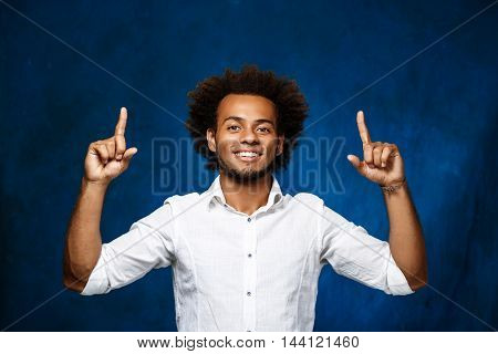 Young handsome african man in white shirt smiling, pointing fingers up over blue background. Copy space.