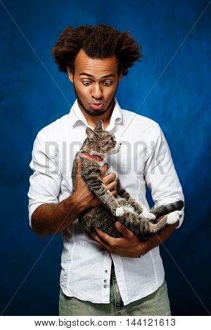 Young handsome african man in white shirt holding cat over blue background. Copy space.