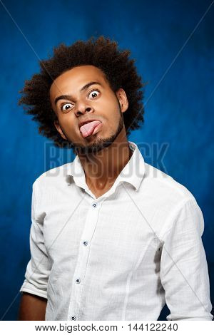 Young handsome african man in white shirt showing tongue, fooling over blue background. Copy space.