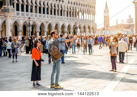 Venice, Italy - May 18, 2016: Venice, Italy - May 18, 2016: Tourist couple make selfie portrait on San Marco square crowded with people. This square is the most popular place among tourists in Venice