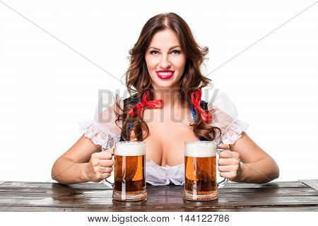 Beautiful young brunette girl in dirndl drinks out of oktoberfest beer stein. Isolated on white background. sits by the table