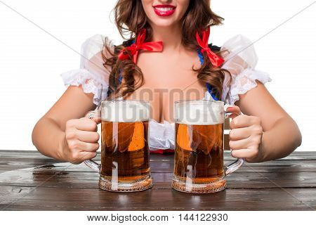 Beautiful young brunette girl in dirndl drinks out of oktoberfest beer stein. Isolated on white background. sits by the table. close up a mugs