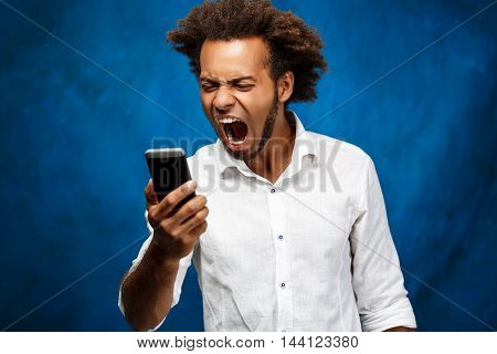 Angry young handsome african man in white shirt looking at phone, shouting over blue background. Copy space.