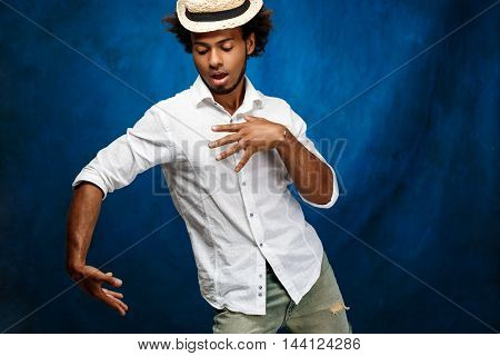 Young handsome african man in white shirt and hat dancing over blue background. Copy space.