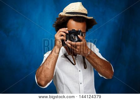 Young handsome african man in white shirt and hat taking photo over blue background. Copy space.