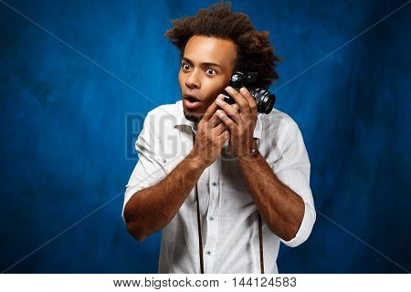 Young handsome african man in white shirt holding old camera, posing over blue background. Copy space.