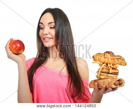 Young woman with fast food and apple. Girl eating hamburger and fries over white background. Healthy and unhealthy eating. Choice, Diet.