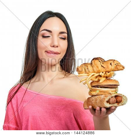 Young woman with fast food. Girl eating hamburger and fries over white background. Unhealthy eating.