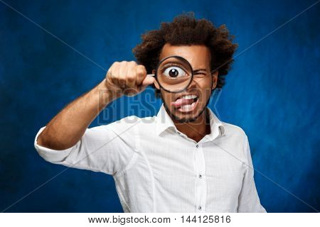 Young handsome african man in white shirt posing with magnifier over blue background. Copy space.