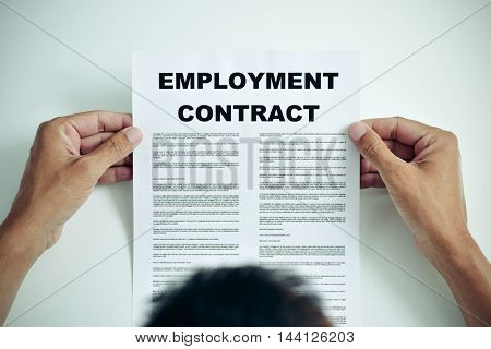 closeup of a young Caucasian man reading the terms of an employment contract
