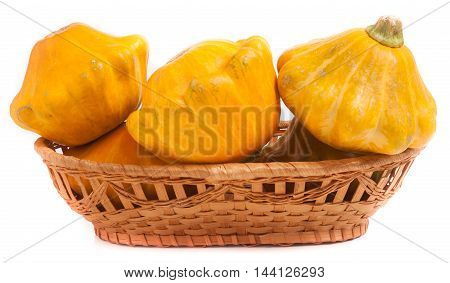 yellow pattypan squash in a wicker basket isolated on white background.