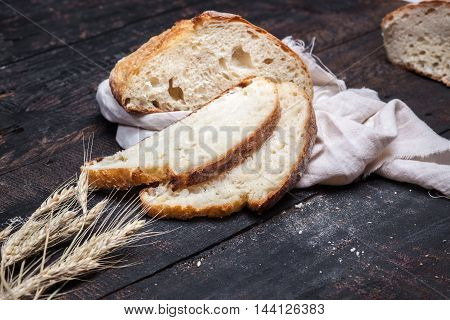 The macro view of rustic bread on an old vintage wooden table. Dark moody background with free text space.