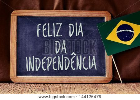 the text Feliz Dia da Independencia, Happy Independence Day written in Portuguese in a chalkboard, and a flag of Brazil, on a rustic wooden surface