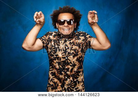 Young handsome african man in sunglasses fooling over blue background. Copy space.