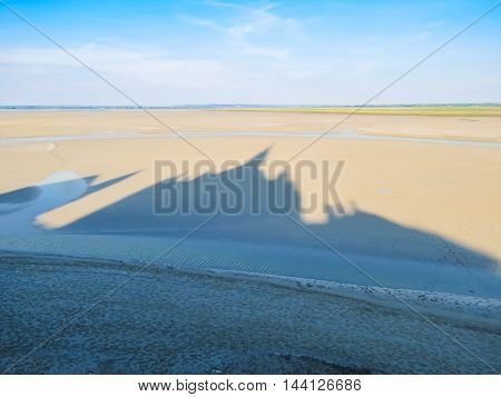 Shadow of Mont Saint-Michel Abbey on a sandy shallow of the bay. France