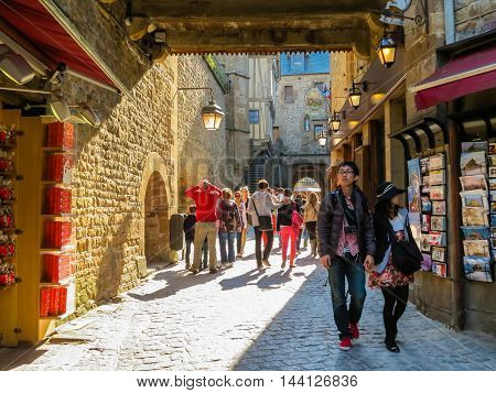 MONT SAINT-MICHEL, FRANCE - MAY 04, 2014: Visitors walk on medieval streets of Mont Saint-Michel, France