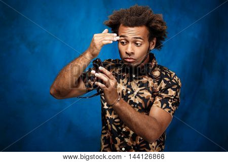 Young handsome african man looking at reflection in sunglasses over blue background. Copy space.