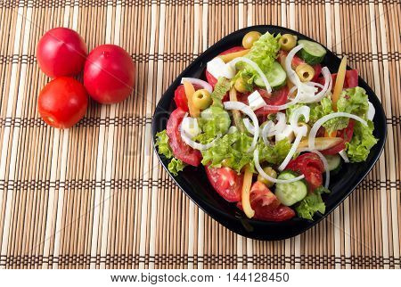 Top View On A Healthy And Natural Vegetable Salad With Tomato, Cucumber, Olives