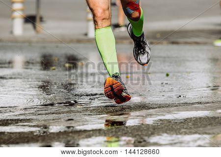 feet men runner's compression socks and knee taping running on wet asphalt