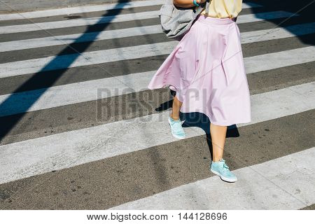 Girl In A Pink Skirt And Sneakers Crossing The Road In The Summer