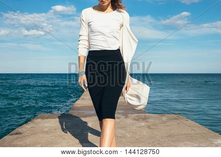 Elegant Woman In A Skirt And Cardigan Walks On The Background Of The Sea On A Sunny Day