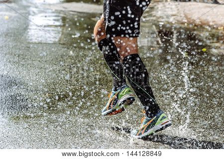 feet men athletic compression socks running in spray of water during sports race