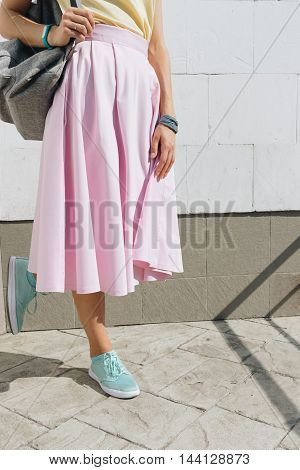 Close-up Of Girl In Pink Skirt, Yellow Shirt And With A Backpack Standing Against A White Wall