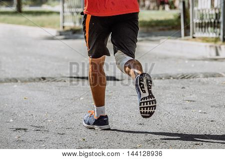 rear view of a man running through streets of city at foot of knee pad